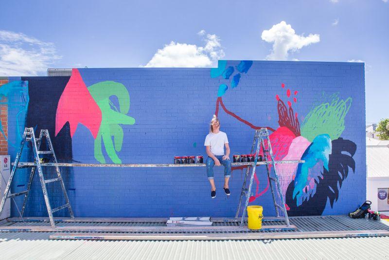 Der Künstler Danny Gretscher vor seinem Wand-Kunstwerk, Foto: Tao Jones